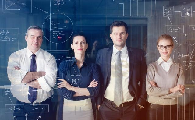 グラフを書いた黒板の前に立つ4人のビジネスパーソン