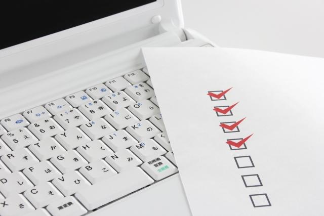 白いノートパソコンの上に置かれたチェックリスト