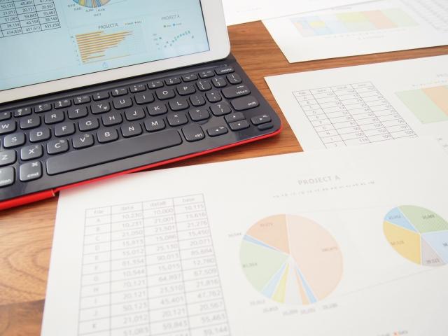 テーブルの上に置いてあるノートパソコンと資料に印刷されたグラフ