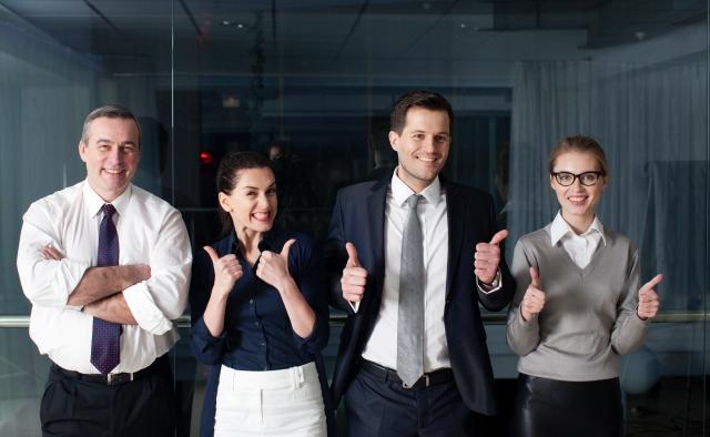 笑顔でグッドサインをする4人の外国人ビジネスパーソン
