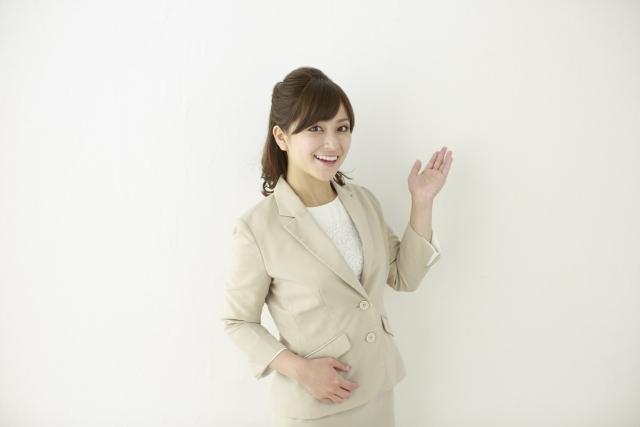 笑顔で左手を挙げて解説する女性