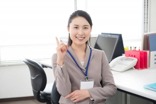 オフィスで笑顔で人差し指を掲げる女性