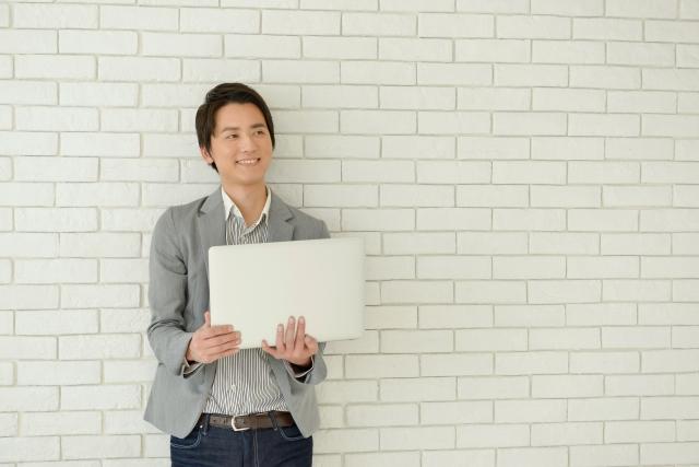 壁を背にしてパソコンを持つ男性