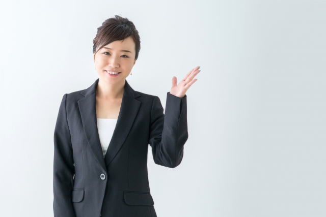 左手を掲げるスーツ姿の女性