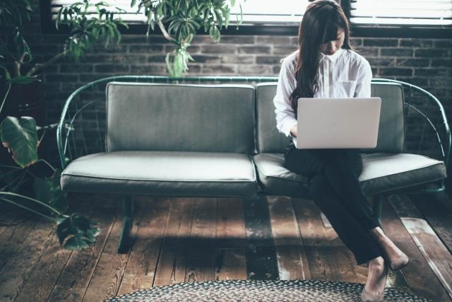 ソファに座ってパソコンで作業をする女性