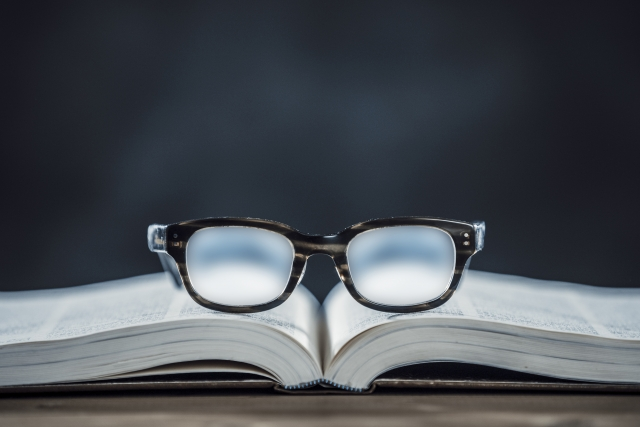 開いた本の上に置いてある眼鏡