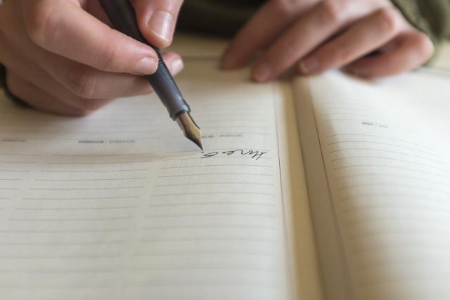 ノートに万年筆で文章を書く人