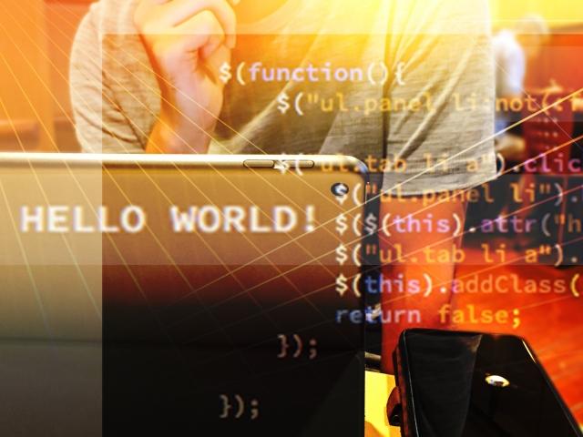 ノートパソコンに向かってプログラミングをする人