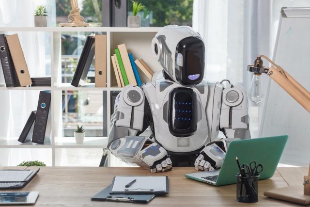パソコンに向かって作業をするロボット