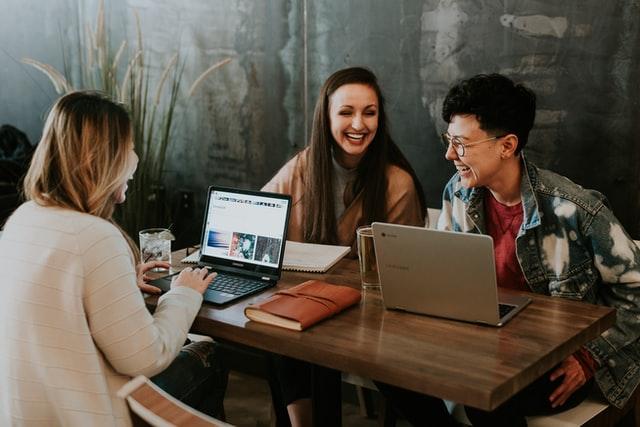 談笑しながらパソコンを操作する3人の男女