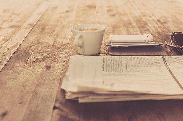 机の上にあるコーヒーと新聞