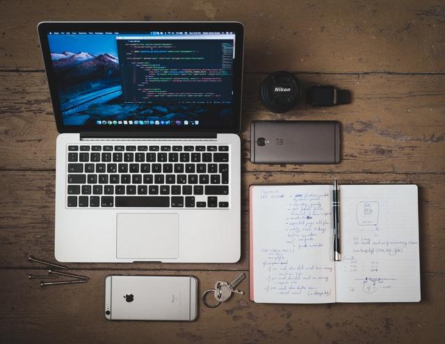 机の上に置いてあるノートパソコンとスマホ、ノート
