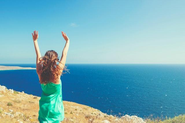 海に向かって両手を挙げる女性